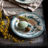 Orthodox Easter table setting with vintage plates with green ornament, forks, dyed eggs, quail eggs, yellow flower. Orthodox Easter table setting with vintage royalty free stock photography