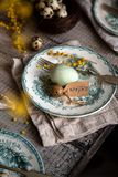 Orthodox Easter table setting with vintage plates with green ornament, forks, dyed eggs, quail eggs, yellow flower stock image