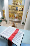 Orthodox Holy Bible on the table. Orthodox Holy Bible laying on the table against the sanctuary Stock Image