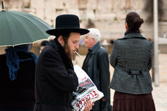 Orthodox jew near Western Wall in Jerusalem, Israel. Jerusalem, Israel - March 24, 2011: Orthodox jew lights a cigarette near Western Wall in Jerusalem Old City Stock Photos