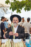 Orthodox Jew with a white beard. JERUSALEM, ISRAEL - OKTOBER 8, 2014: Traditional market before the holiday of Sukkot. Orthodox Jew with a white beard in a black Stock Photos