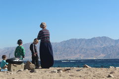Orthodox jewish family on the beach in Eilat, Israel Stock Images