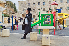 Orthodox Jewish man with mobile phone walk at playground in jewi Royalty Free Stock Photography