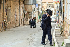 Orthodox Jewish man with mobile phone walk at street of Jerusale Stock Images