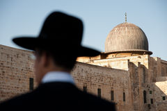 Orthodox Jews and Al-Aqsa Mosque. JERUSALEM - AUGUST 24: Ultra-orthodox Jews stand silhouetted against the dome of the Al-Aqsa Mosque in Jerusalem's Old City Stock Photo