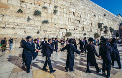 Orthodox Jews in Jerusalem. Jerusalem, Israel - October 22, 2015. Group of Orthodox Jews dances next to ancient limestone wall known as Wailing Wall in the Old Royalty Free Stock Photo