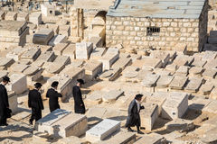 Orthodox Jews walking among graves on the Mount of Olives Royalty Free Stock Images