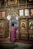 Orthodox liturgy with bishop Mercury in Moscow. MOSCOW - MARCH 13: The priests reads prayer in front of iconostasis during the Orthodox liturgy with bishop Royalty Free Stock Photo