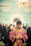 Orthodox liturgy with bishop Mercury in Moscow. MOSCOW - MARCH 13: The lay brother droops his head and prays with the parishioners at the background during the Stock Photos