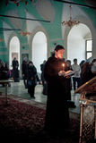 Orthodox liturgy with bishop Mercury in Moscow. MOSCOW - MARCH 13: The monk reads the Bible with a burning candle in his hands during Orthodox liturgy with Royalty Free Stock Images