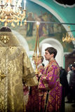 Orthodox liturgy with bishop Mercury in Moscow. MOSCOW - MARCH 13: The lay brother stands near the bishop and holds triple candelabrum during the Orthodox Stock Image
