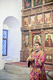 Orthodox liturgy with bishop Mercury in Moscow. MOSCOW - MARCH 13: The lay brother stands in a front of iconostasis and holds double candlestick during the Royalty Free Stock Photos