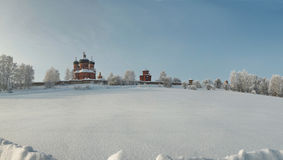 Orthodox monastery amidst hoary forest in deep snow area Royalty Free Stock Photography