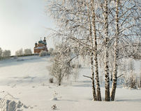 Orthodox monastery behind of bare birches in deep snow Royalty Free Stock Photo