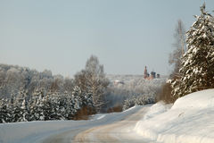 Orthodox monastery in the heart of the winter forest with snow covered road and fir trees Stock Photos