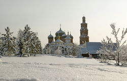 Orthodox monastery with snow covered domes in snowy area with bare trees.  Stock Images