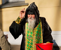 Orthodox monk hood blesses people outside Stock Image