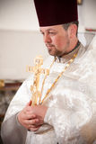 Orthodox priest holding candles and crucifix Royalty Free Stock Photography