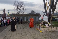 Orthodox priest makes a memorial service and people with white balloons on the day of mourning for those killed in a fire in Kemer. Adygea, Russia - March 28 Stock Photography