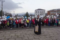 Orthodox priest and people with white balloons on the day of mourning for those killed in a fire in Kemerovo. Adygea, Russia - March 28, 2018: Orthodox priest Stock Photos