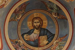 Orthodox religious christian art depicting Jesus Christ. Artwork in the monastery at the mountain of temptation. Jesus holding a bible, surrounded by angels Royalty Free Stock Image