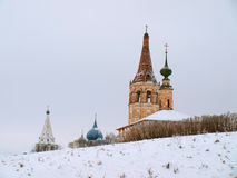 Orthodox Russia. Churches. Suzdal - one of cities of the Gold Ring of Russia in the winter. Domes and belltowers of churches behind ancient defensive shaft. In royalty free stock images