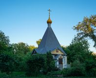 Orthodoxe hölzerne Kapelle hiiden in den grünen Bäumen stockfotos