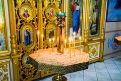 Orthodoxe kerk van de binnenkant Brandende kaarsen voor pictogrammen en fresko's Christelijke godsdienst Stock Foto