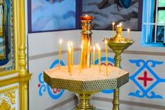 Orthodoxe kerk van de binnenkant Brandende kaarsen voor pictogrammen en fresko's Christelijke godsdienst Stock Foto's
