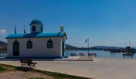 Orthodoxe Kirche Aghios Nikolaos und Mittelmeerfischerboote auf Wasser in Euboea - Nea Artaki, Griechenland lizenzfreies stockbild