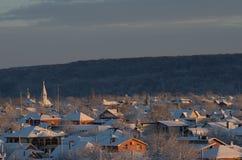 Orthodoxe Kirche unter den einstöckigen Häusern Sonnenuntergang auf den des Urals Bergen Lizenzfreie Stockfotografie