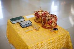 Orthodoxe Utensilien der kirchlichen Hochzeit auf Tabelle - Kreuz, Bibel und Kronen Lizenzfreie Stockbilder
