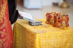 Orthodoxe Utensilien der kirchlichen Hochzeit auf Tabelle - Kreuz, Bibel und Kronen Stockfoto