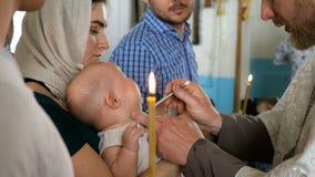 Orthodoxer Priester tauft ein Kind mit Weihwasser Mutter ` s H?nde, die Baby halten Sakrament der Taufe Kind und Gott Kerze für c stock footage