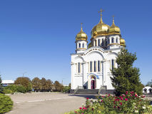 Orthodoxy Church Temple with golden domes. Holy Protection of the Mother of God. Angle view. Greenery with red roses and blue sky around it. Donetsk, Ukraine stock images