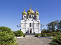 Orthodoxy Church Temple with golden domes. Holy Protection of the Mother of God. Front view. Greenery with red roses and blue sky around it. Donetsk, Ukraine royalty free stock image