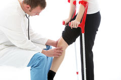 Orthopaedic surgeon examining woman's knee. Orthopaedic surgeon sitting examining the knee of a female patient on crutches following surgery for a joint injury Royalty Free Stock Image