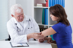 Orthopaedist diagnosing painful elbow. Of young patient Royalty Free Stock Photography