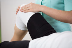 Orthopedic diagnosing painful knee. Of young woman royalty free stock photography