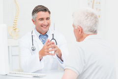 Orthopedic doctor discussing with senior patient. Male orthopedic doctor discussing with senior patient in clinic Royalty Free Stock Image