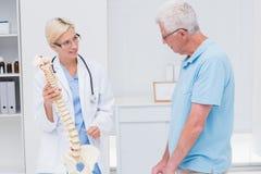 Orthopedic doctor explaining anatomical spine to senior man. Female orthopedic doctor explaining anatomical spine to senior men in clinic Stock Photography