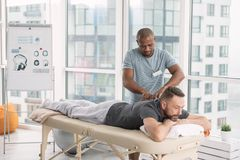 Skillful strong man doing spine massage royalty free stock photography