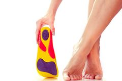Orthopedic insoles and female feet stock images