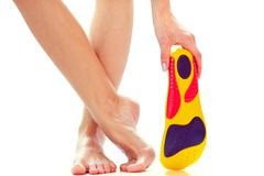 Orthopedic insoles and female feet. Orthopedic insole in the hand and female feet stand on tiptoe stock photos