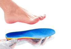 Orthopedic insole in the hands. Hands in rubber gloves hold an orthopedic insole stock photography