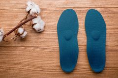 Cotton branch and orthopedic insoles on a wooden table royalty free stock image