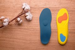 Cotton branch and orthopedic insoles on a wooden table royalty free stock photography