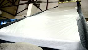 Orthopedic mattresses move along conveyor belt at factory indoors. stock footage