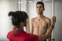 Posture and equilibrium analysis of body growth. Orthopedic physiotherapist check body growth of young athlete royalty free stock images