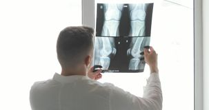 Orthopedic surgeon diagnostics damage of bones on x-ray images standing near the window, back view.